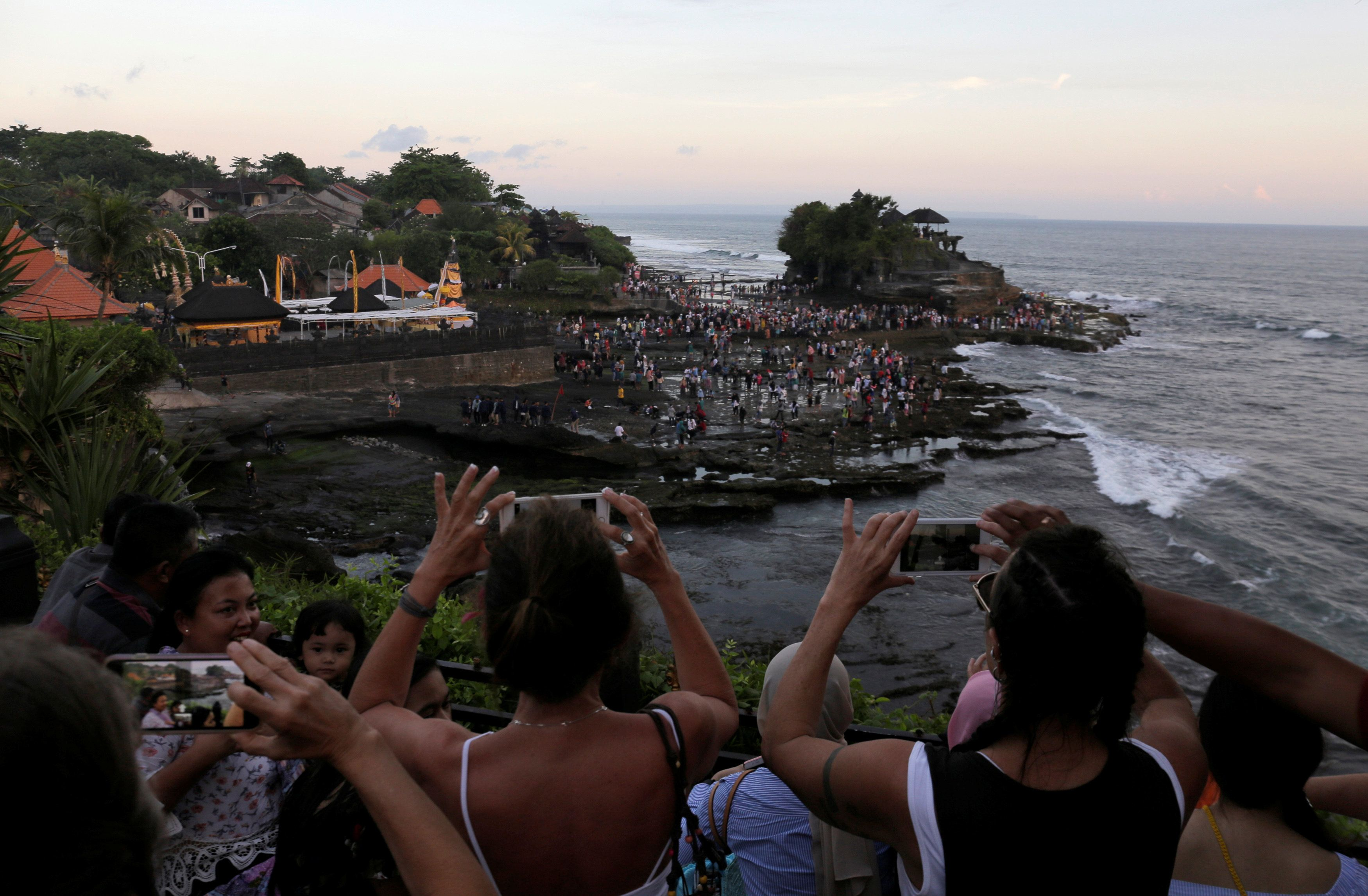 Tourists take pictures of the Hindu temple Tanah Lot (R) in Tabanan, on the resort island of Bali, Indonesia May 6, 2018.  REUTERS/Johannes P. Christo