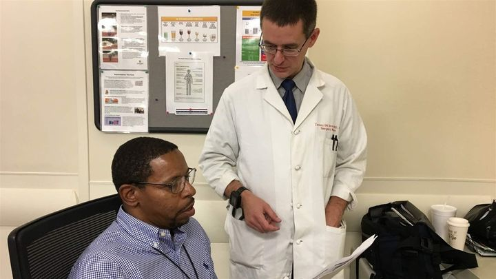 Recovery coach Dwayne Dean, left, and Dr. Zachary Dezman confer about a patient at the University of Maryland Medical Center