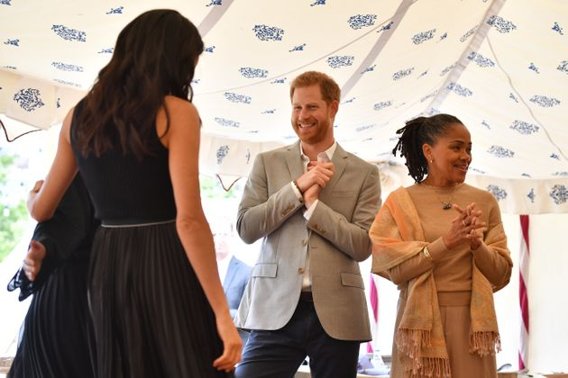 The Duke of Sussex looks at Meghan, Duchess of Sussex, during her first solo royal hosting event. Meghan's...