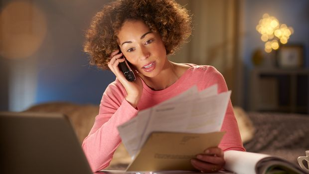 a young woman sits at home , going through her paperwork and bills .she is working at her laptop and is speaking to someone on the phone about her bills . She could be running her own business or just keeping up with the household accounts but she does not look happy .