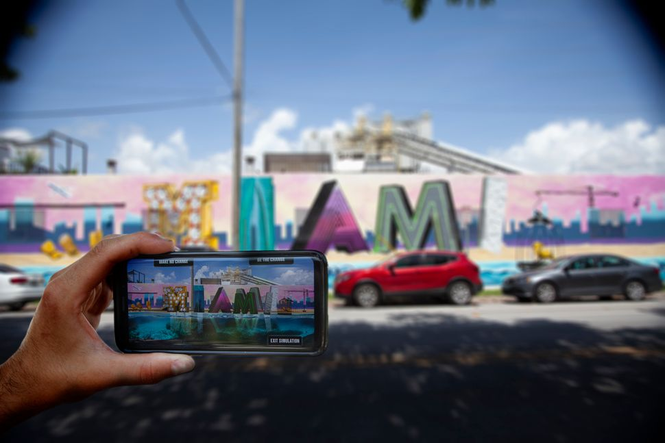 A viewer uses their smartphone to view 'What Future Do You Choose for Miami?', an augmented reality mural in the