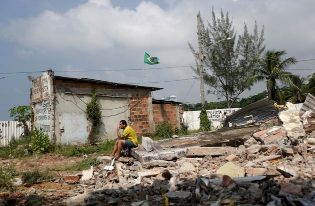 A man sits atop the rubble of his home in Vila Autodromo, a Rio de Janeiro neighborhood that was destroyed...