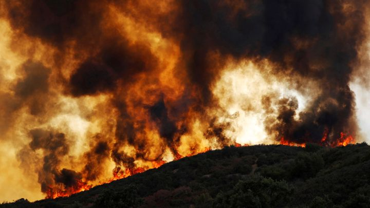 Wind-driven flames roll over a hill toward homes during the River fire near Lakeport, California, on Aug. 2.