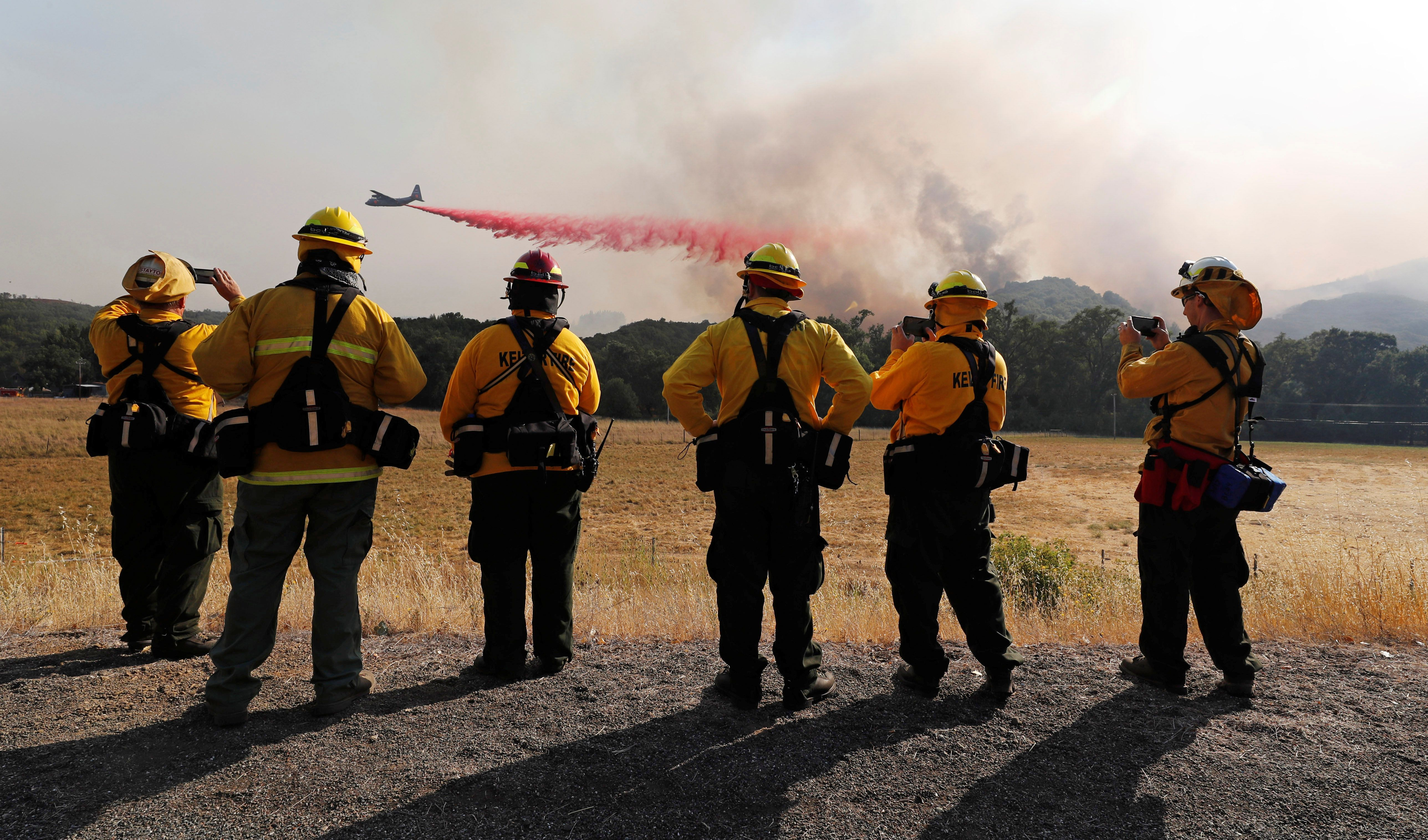 Firefighters watch as an air tanker drops fire retardant to protect homes along the crest of a hill at the River Fire (Mendocino Complex) near Lakeport, California, U.S. August 2, 2018.  REUTERS/Fred Greaves