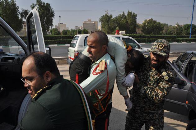 Des militaires iraniens transportent leur camarade blessé dans l'attaque à Ahvaz au sud-ouest...