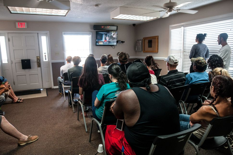 Patients watch watch TV while waiting for their number to be called to receive their medication at Carolina Treatment Center