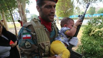 An image made available by Iran's Mehr News agency on September 22, 2018, shows an Iranian soldier carrying a child at the site of an attack on a military parade in the southwestern Iranian city of Ahvaz, that was marking the anniversary of the outbreak of its devastating 1980-1988 war with Saddam Hussein's Iraq. - Dozens of people were killed with dozens others wounded in an attack in the southwestern Khuzestan province on September 22 targeting on an army parade commemorating the anniversary of the 1980-1988 Iran Iraq war, state media reported. (Photo by Mehdi Pedramkhou / various sources / AFP)        (Photo credit should read MEHDI PEDRAMKHOU/AFP/Getty Images)