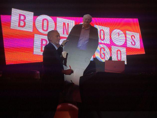 Jeremy Corbyn signs a cardboard cutout of Jeremy Corbyn.