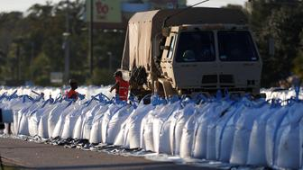 Members of the National Guard work on a long sand bag flood barrier being built by the South Carolina Department of Transportation on U.S. 501 to lesson damage to roads anticipated from floods caused by Hurricane Florence, now downgraded to a tropical depression, in Conway, South Carolina, U.S. September 19, 2018. REUTERS/Randall Hill