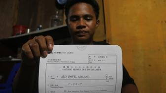 This picture taken in Wori, North Minahasa, Sulawesi on September 16, 2018 shows Indonesian teenager Aldi Novel Adilang showing a letter of landing permit due to disaster in Wori. - An Indonesian teenager survived seven weeks adrift at sea after his tiny fishing trap lost its moorings and ended up some 2,500 kilometres (1,500 miles) away in waters near the Pacific island of Guam, his family said on September 24. (Photo by STR / AFP)        (Photo credit should read STR/AFP/Getty Images)