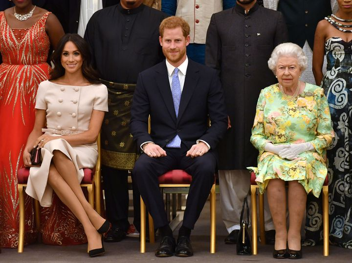 Queen Elizabeth, Prince Harry and Meghan, the Duchess of Sussex pose for a picture with some of Queen's Young Leaders at a Bu