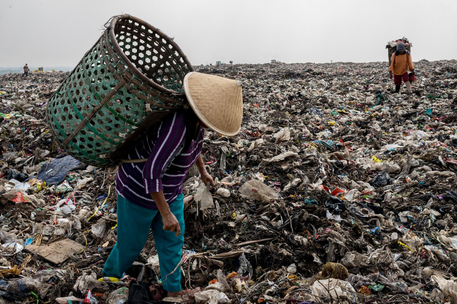 "Mak Muji, 55, picks up plastics and other materials on the top of the mountain of garbage in ""Bantar Gebang"", the landfill for solid waste of Jakarta, a city of more than 15 million residents. Every day, at dawn, she crosses the road in front of her village and goes to the dumping site for collecting trash, mostly plastics but also glass, cans, shoes, iron. She puts everything in her back pannier to sort them later and sell to recycling factories. Bekasi, Indonesia, 19th September 2017."