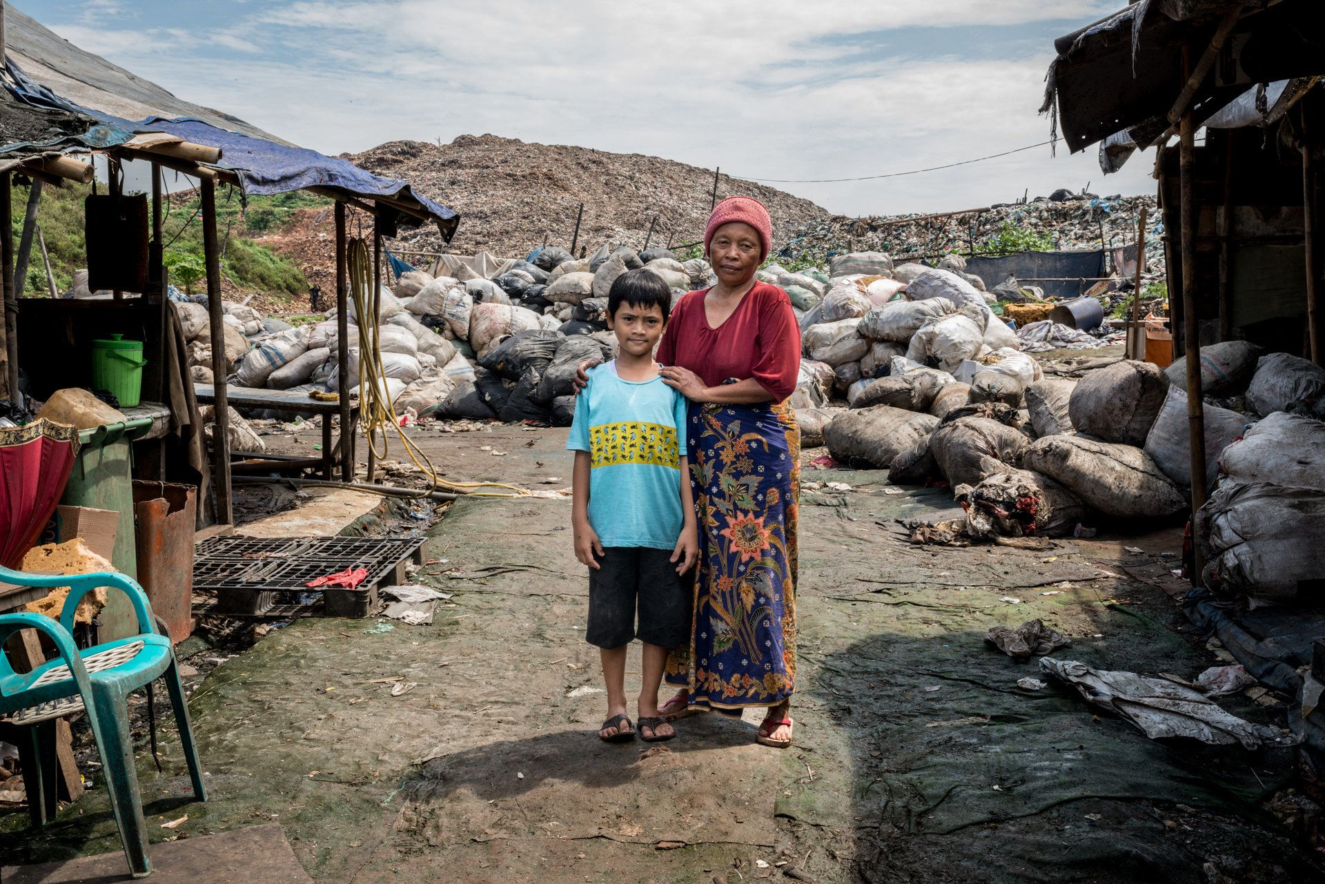 Reza, left, with Mak Muji, the midwife who helped deliver him, in front of his family's shack.