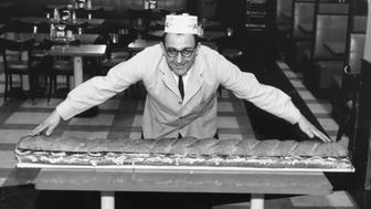 15th April 1966:  James Dellorto, whose family has been in the restaurant and food business for over 100 years in Sorrento, Italy, specialises in enormous sandwiches. This one is six feet long.  (Photo by F. Roy Kemp/BIPs/Getty Images)