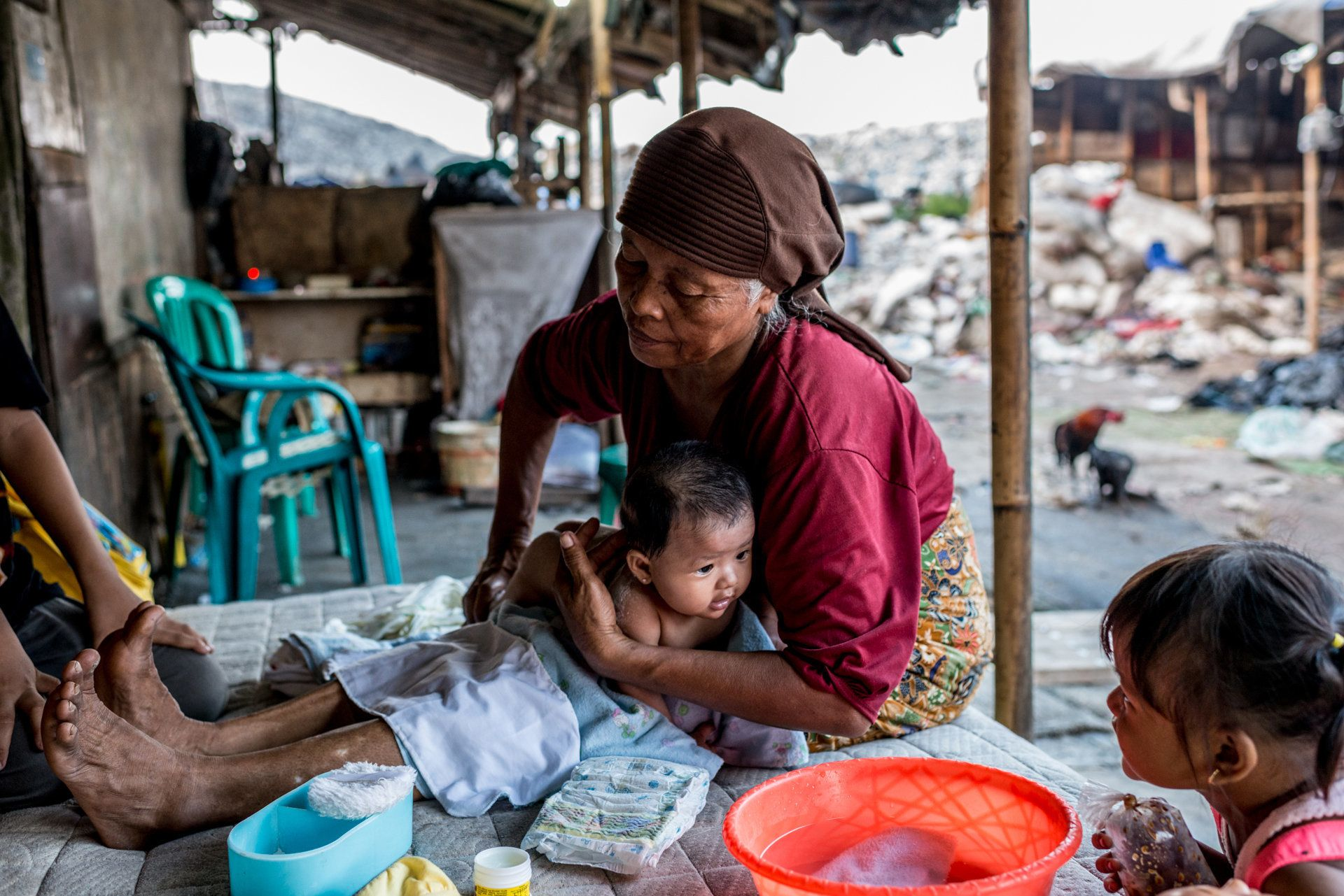 Mak Muji washes Reza's sister, Aysila Husna, 3 months old. Mak Muji did not deliver the newborn because the family had enough
