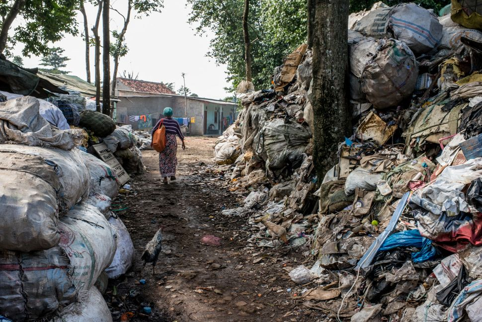 Mak Muji walks through heaps of waste on her way to one of the landfill villages. The orange bag slung...
