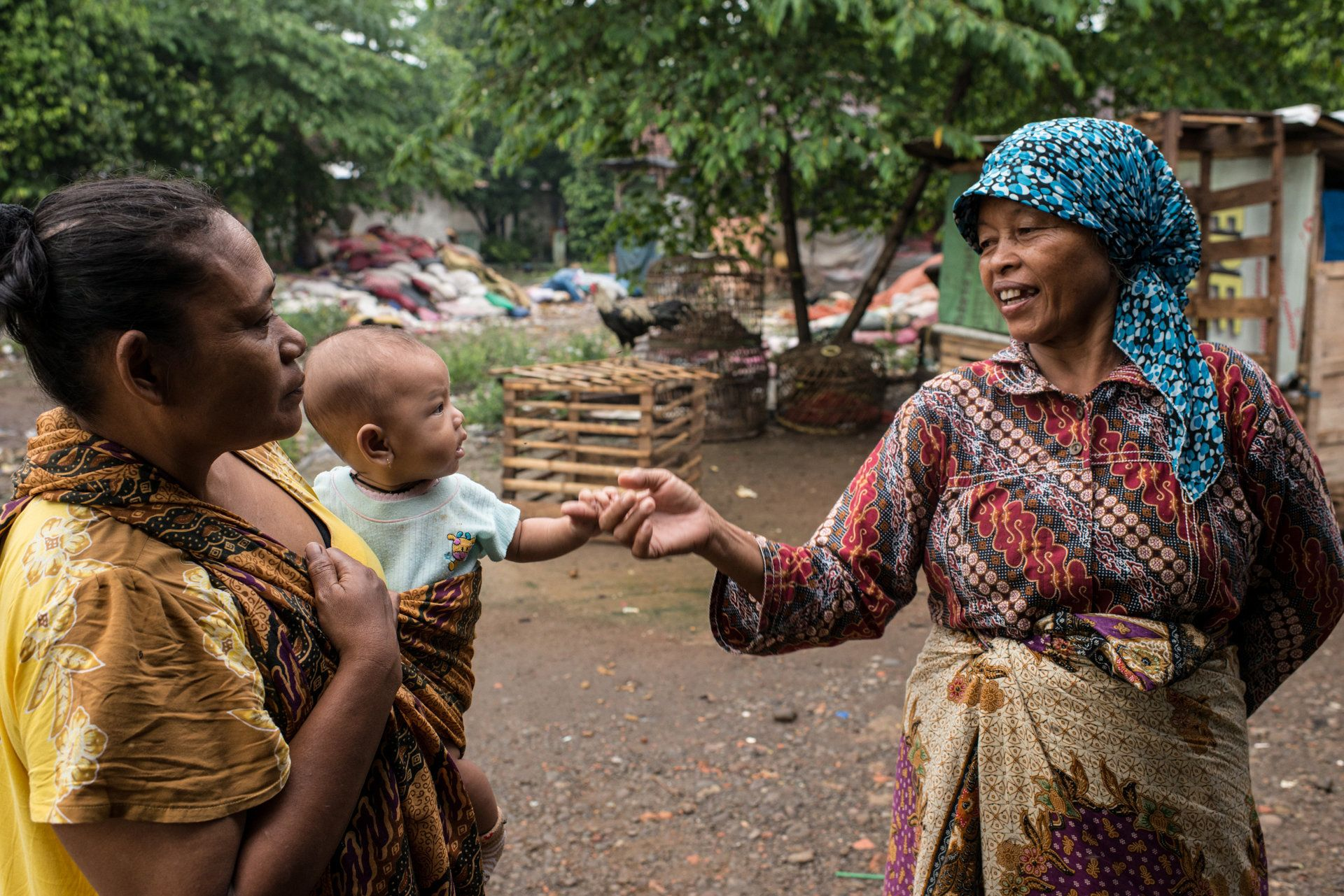 Mak Muji, on a stroll through her village, greets a mother holding a baby she helped deliver.