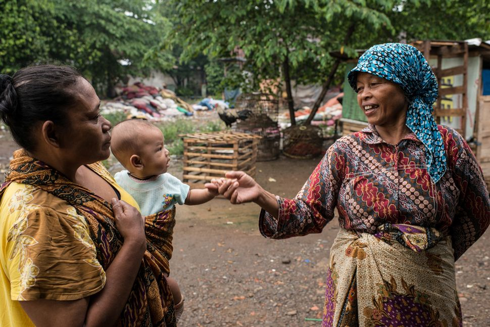 Mak Muji, on a stroll through her village, greets a mother holding a baby she helped