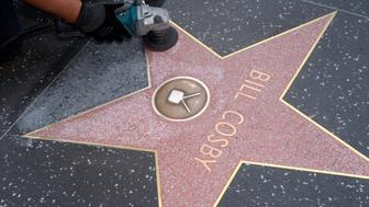A worker cleans graffiti on actor Bill Cosby's star on the Hollywood Walk of Fame in Los Angeles December 5, 2014.  REUTERS/Phil McCarten (UNITED STATES - Tags: ENTERTAINMENT CRIME LAW)