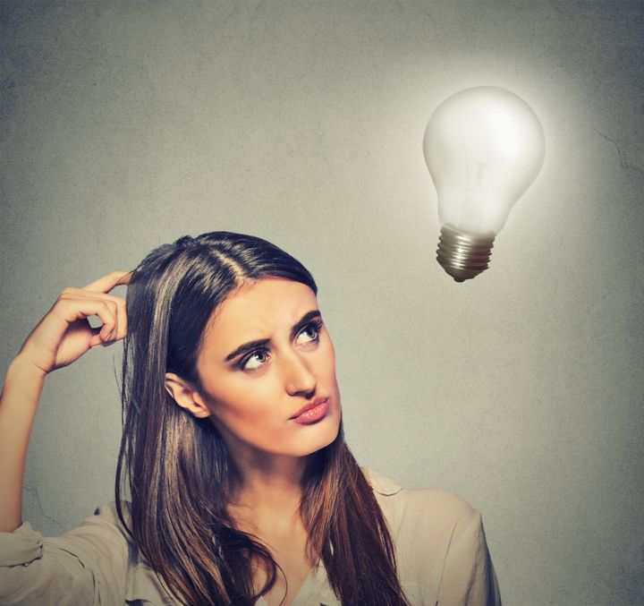 Closeup portrait beautiful girl woman thinks looking up at bright light bulb isolated on gray wall background. Idea, business