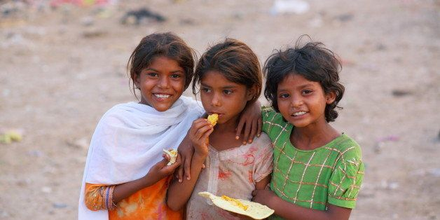 Poor girls living at the bank of Ravi River Near Lahore, might be the poorest area, are Smiling after receiving the Roti (bre