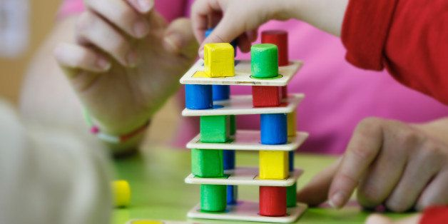 Children playing with homemade, do-it-yourself educational toys, stacking and arranging colorful pieces. Learning through exp