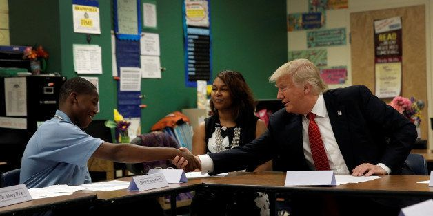 Republican presidential nominee Donald Trump shakes hands with 12 year old student Egunjobi Songofunmi during a campaign visi