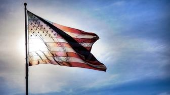 Bright sunlight shines through a backlit, fluttering flag of the United States of America.