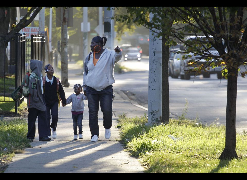 Leslie Sabbs-Kizer, right, walks her children Nkai Melton, 8, Akaira Melton, 7, and Khaymya Smith, 3 to Bond Elementary schoo
