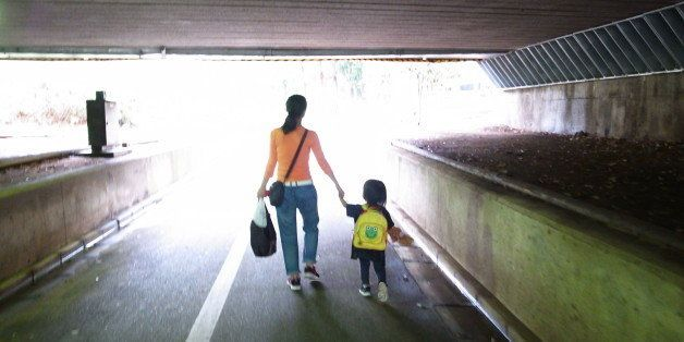 Mother and child walking on road.