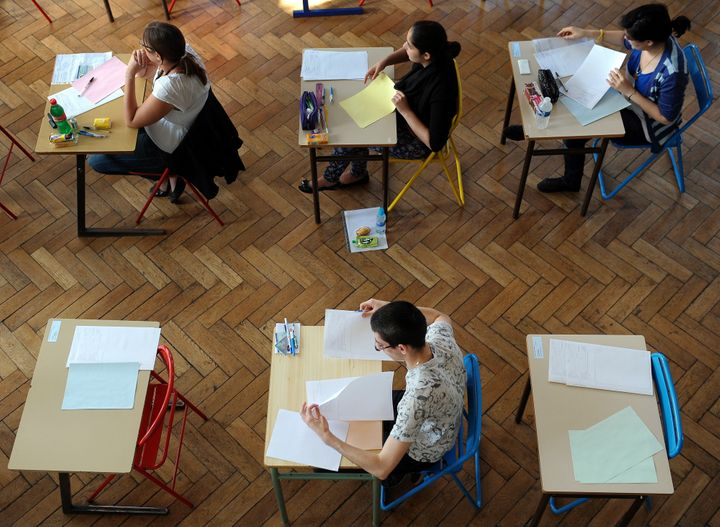 French students work on the test of Philosophy as they take the baccalaureat exam (high school graduation exam) on June 18, 2