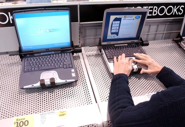 402026 07: A man tests a Compaq laptop that sits next to a Hewlett Packard laptop on display at a Best Buy store March 7, 200