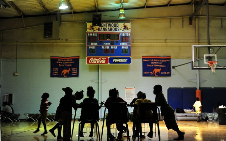 Children try to do their homework at an evacuation shelter in a high school gymnasium in Kentwood, northeast of New Orleans o