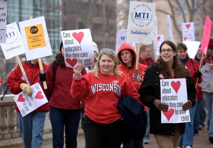 MADISON, WI - FEBRUARY 16: Teacher Cyndi Ehrhart (L) and Anne McClure (R) join protesters marching at the State Capitol building on February 16, 2010 in Madison, Wisconsin. Protesters were demenstrating against Wisconsin Gov. Scott Walker's proposal to eliminate collective bargaining rights for many state workers. (Photo by Mark Hirsch/Getty Images)
