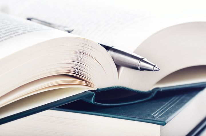close up of open book and pen