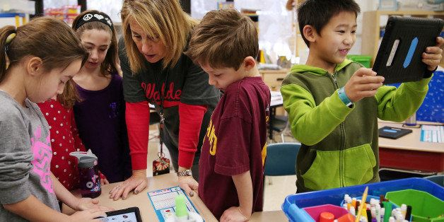 Andrew Zhu, right, smiles while using his iPad for a lesson as first grade teacher Jan Sabin helps Hayden Putz, left, with he