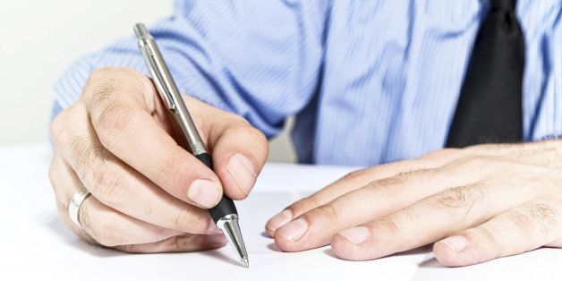 Businessman signing contract. Business man in blue shirt is signing agreement document.