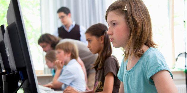 Male teachers helping pupils in computer room, Hamburg, Germany