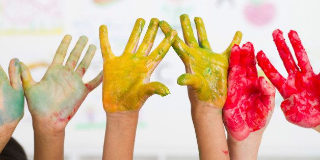 kids hands covered with paint in classroom