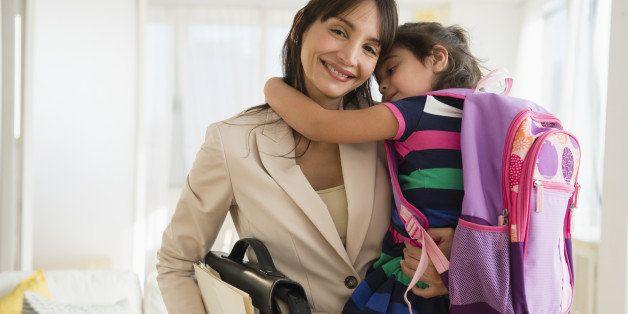 Hispanic daughter hugging mother as she leaves for work