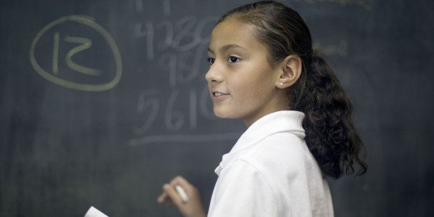 Ten year old Hispanic girl solves math problem in classroom.
