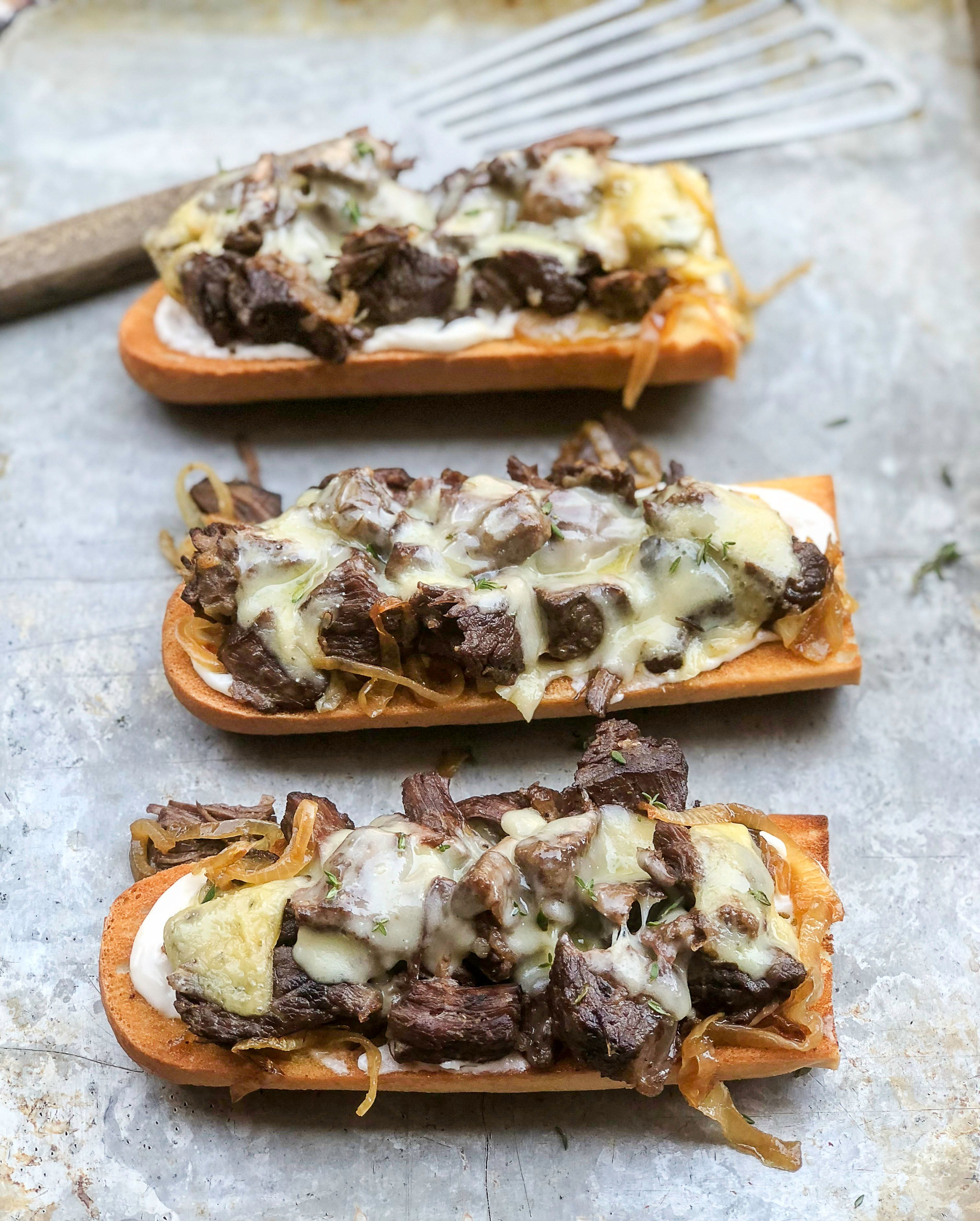 Toasted baguettes slathered in horseradish mayo, topped with roast beef, caramelized onions and cheese (in this case, raclette).