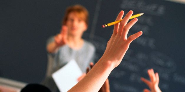 Teacher pointing to raised hands in classroom