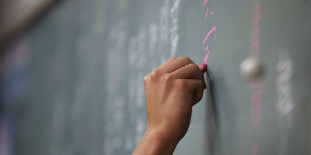 A teacher writes on a chalkboard during a class at the Korean High School in Tokyo, Japan, on Thursday, Sept. 25, 2014. The s