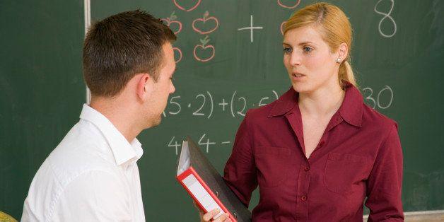 Teacher talking to man in class