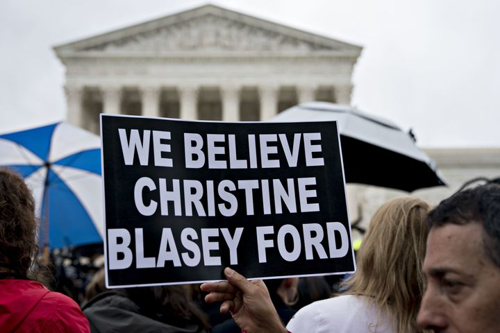"A demonstrator holds a ""We Believe Christine Blasey Ford"" sign outside the U.S. Supreme Court in Washington on Sept. 24.&nbsp"