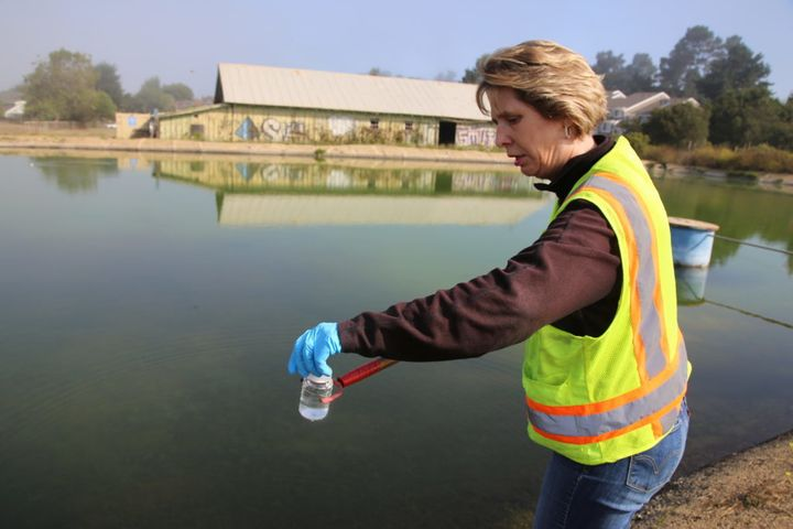 <em>Kara Waugaman collects a water sample from a concrete-lined reservoir at Seascape Ranch near Watsonville, Calif. Over yea