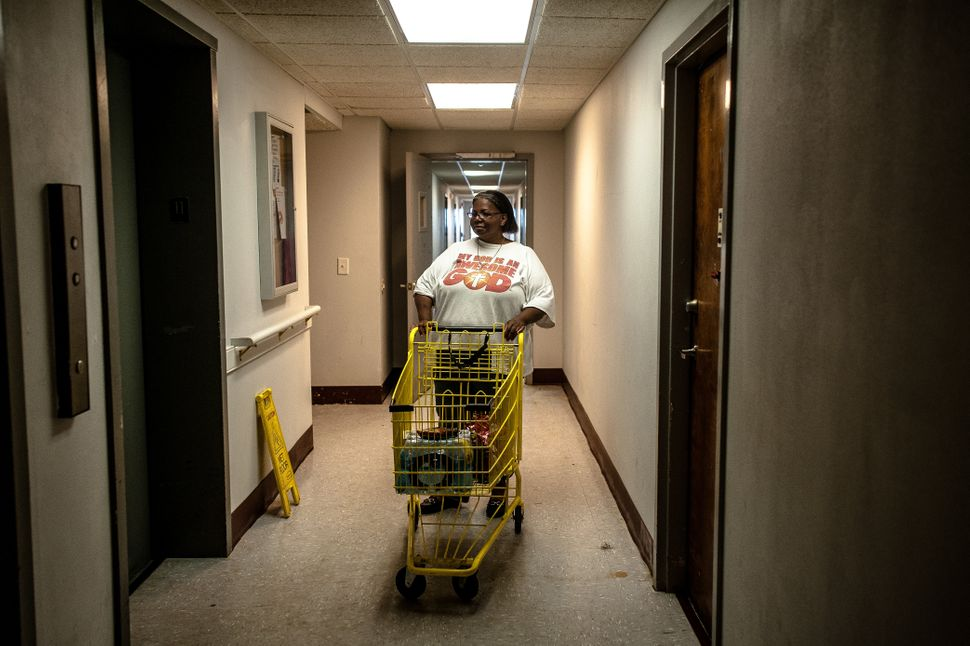 Debbie Williams takes food and water brought in by the Wilmington Police Department to her 11th-floor apartment.