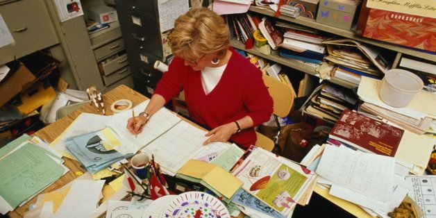 Primary school teacher working at crowded desk in cramped office