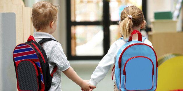 Two cute little children walking to school - Rear view
